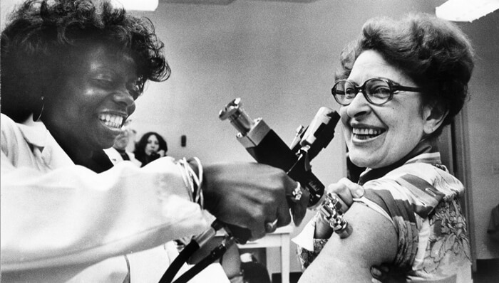 A vintage black and white photo of a nurse administrating a swine flu vaccination with an auto injector