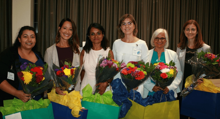 The six panelists all stand together holding flowers from the PDA West Coast Chapter at the event