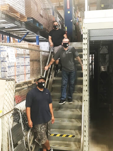 3 member volunteers on a warehouse staircase wearing PDA facemasks